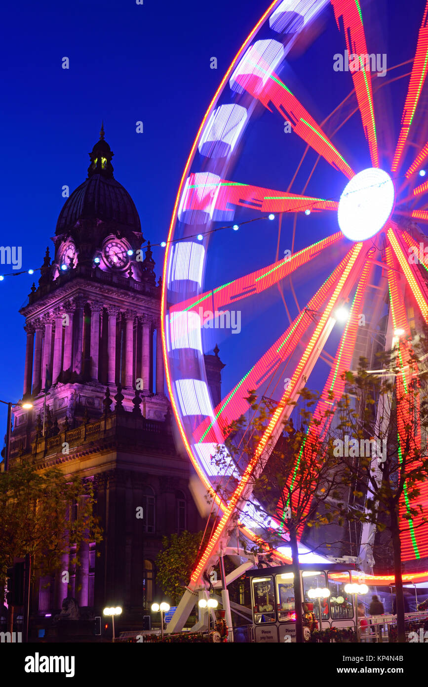 traffic passing funfair and christmas lights by leeds town hall at twilight yorkshire united kingdom - Stock Image