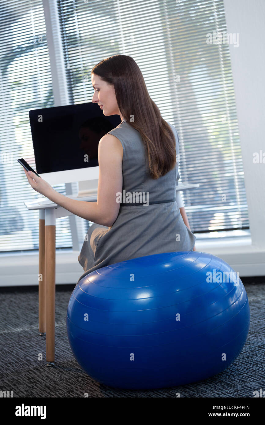 Wondrous Rear View Of Female Executive Sitting On Exercise Ball While Home Interior And Landscaping Ponolsignezvosmurscom