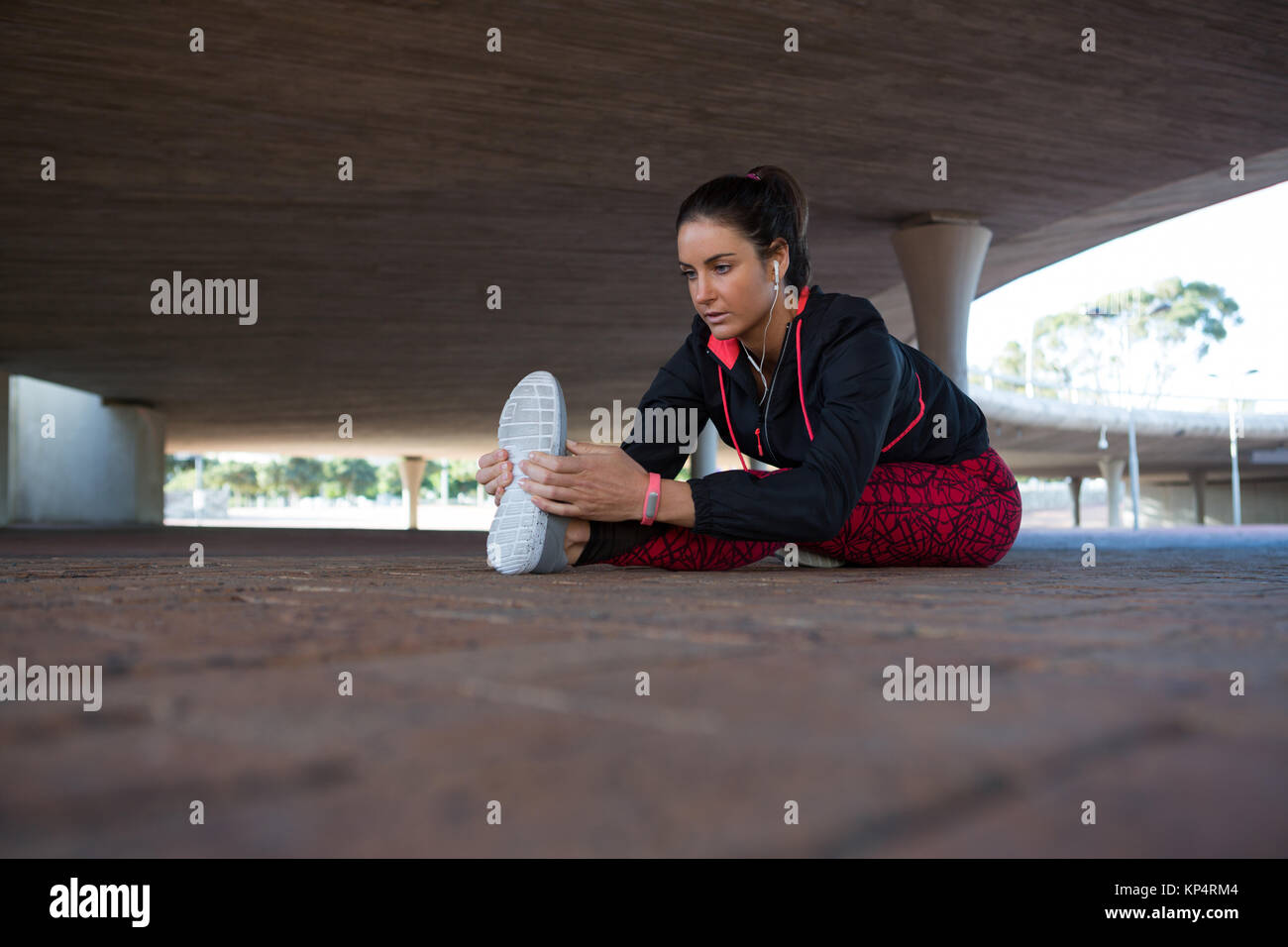 Fit woman doing warm up under bridge - Stock Image