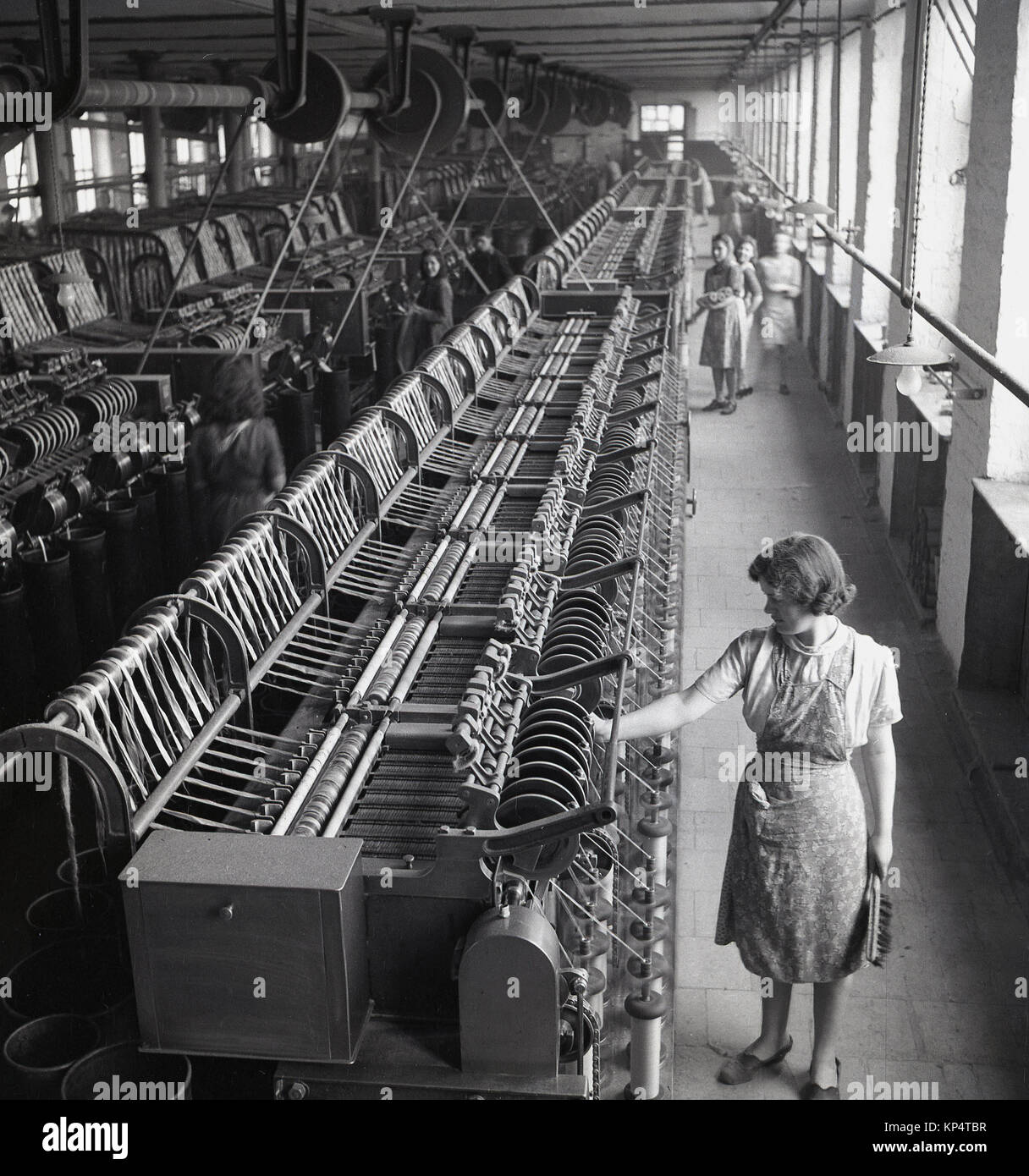 1950s, historical, picture shows rows of mechanised weaving machines, the female operatives and one of the female - Stock Image