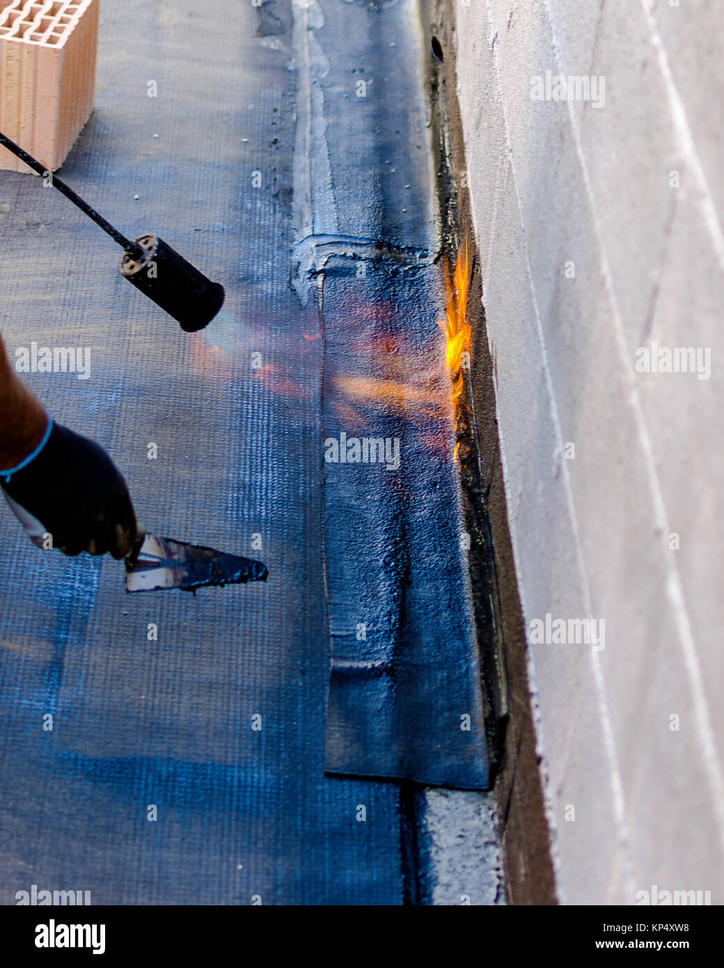 Roofer installing rolls of bituminous waterproofing membrane for the