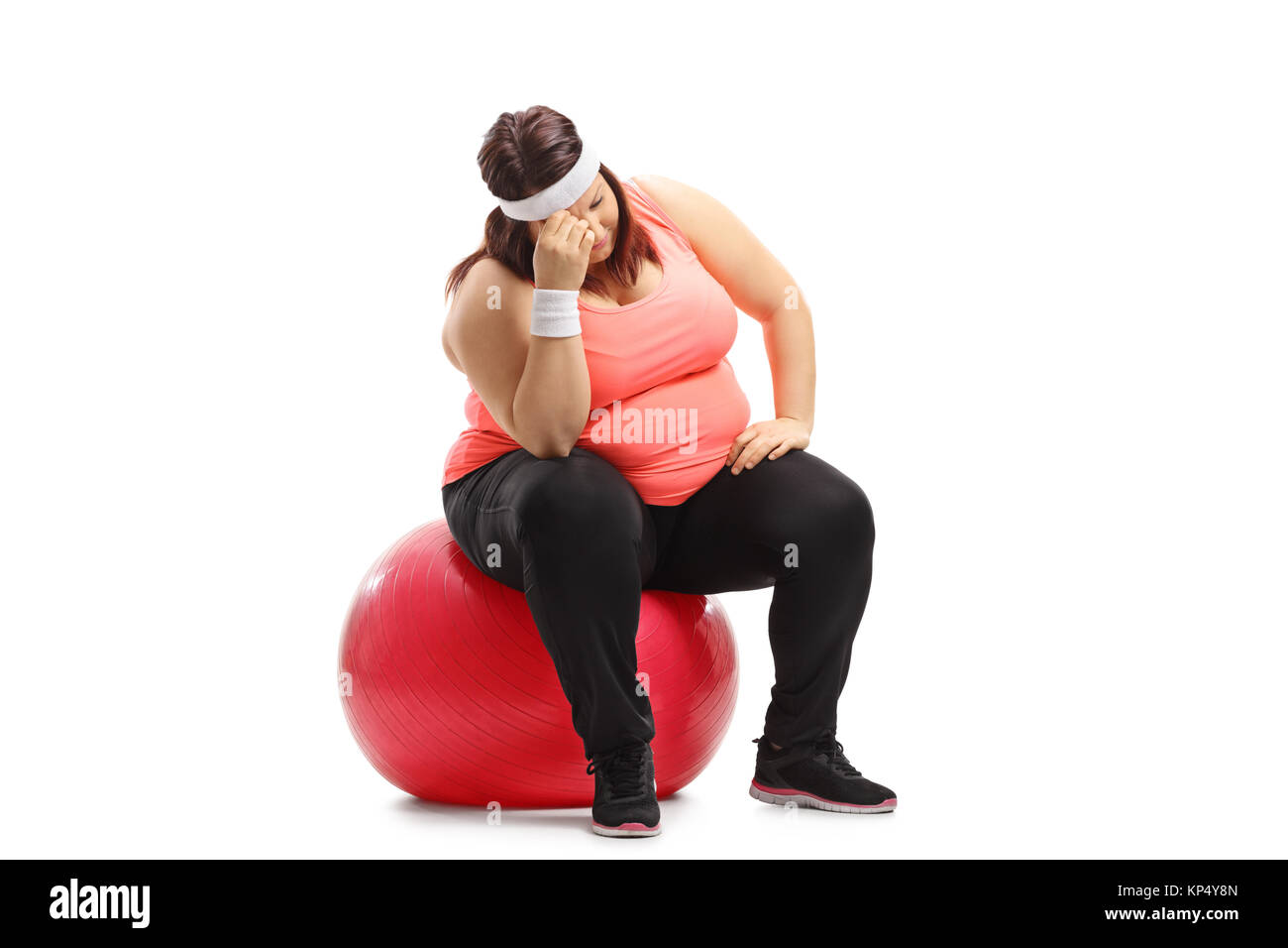 Sad overweight woman sitting on an exercise ball isolated on white background Stock Photo