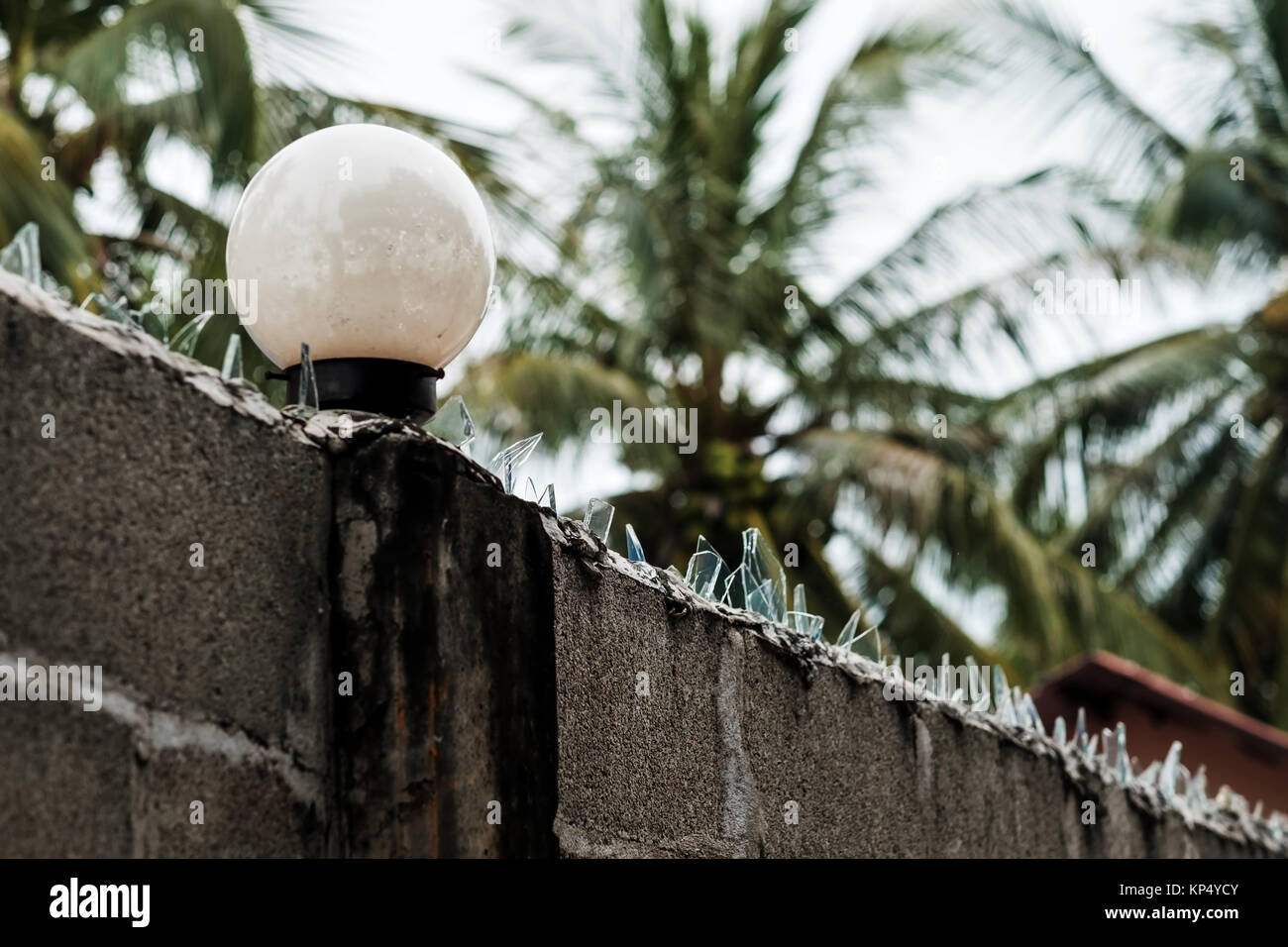 Fence in the Vietnamese village. Sharp glass fragments, like protection from thieves - Stock Image