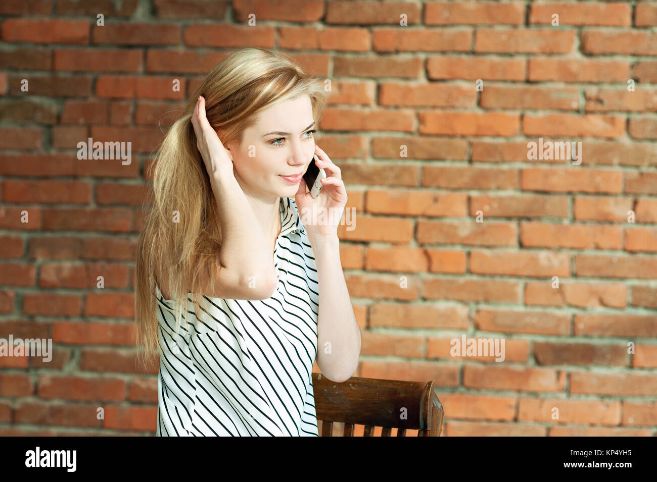 A blonde girl is calling by the phone against a brick wall background, calling the apartment repair service. Advertising Stock Photo