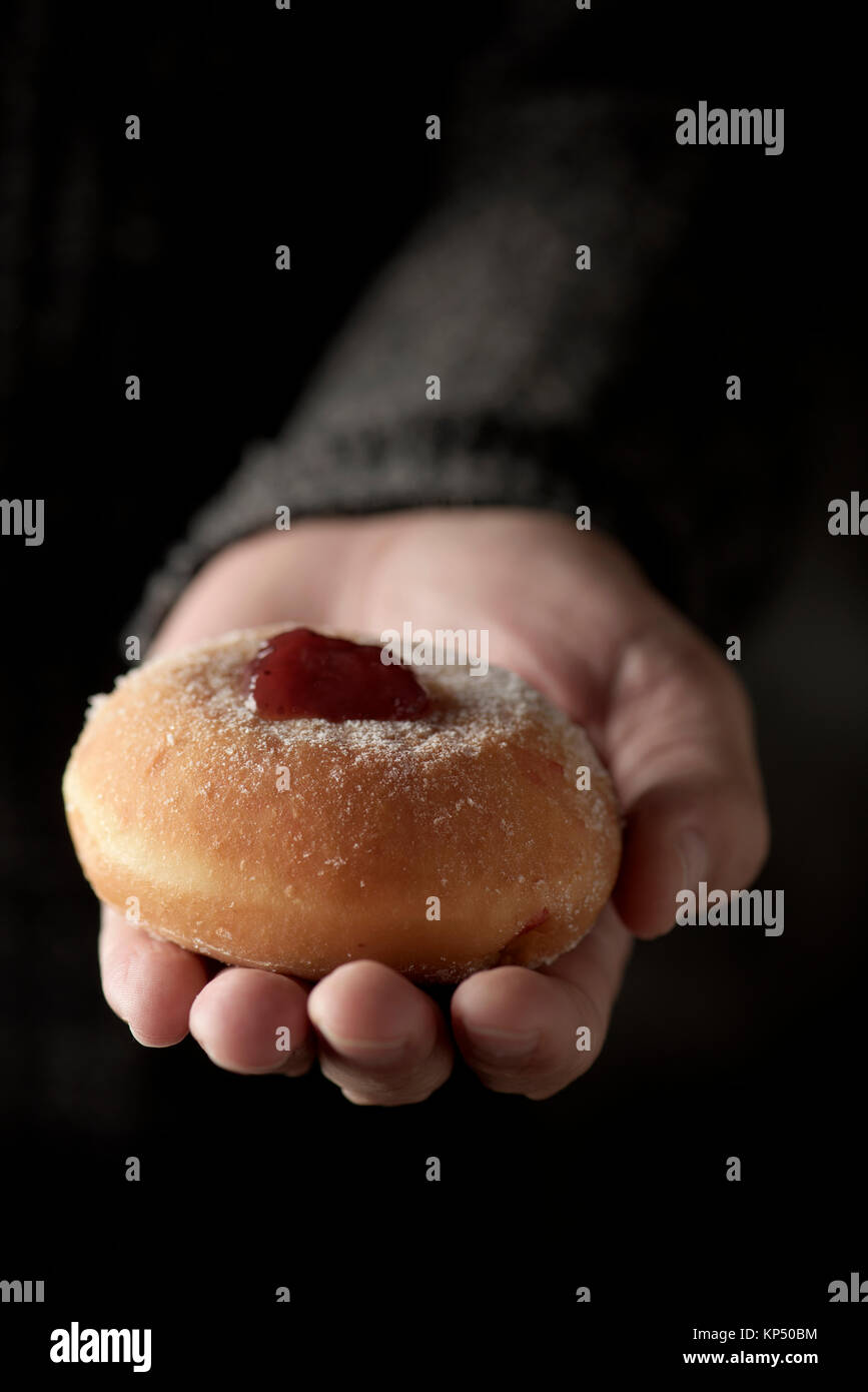 closeup of a sufganiyah, a Jewish donut filled with strawberry jelly traditionally eaten on Hanukkah, in the hand - Stock Image