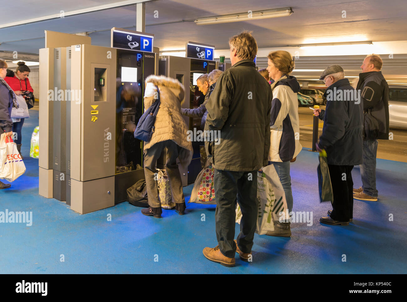 Queue of people in a multi-storey car park in the UK waiting to buy a ticket from parking ticket machines. - Stock Image
