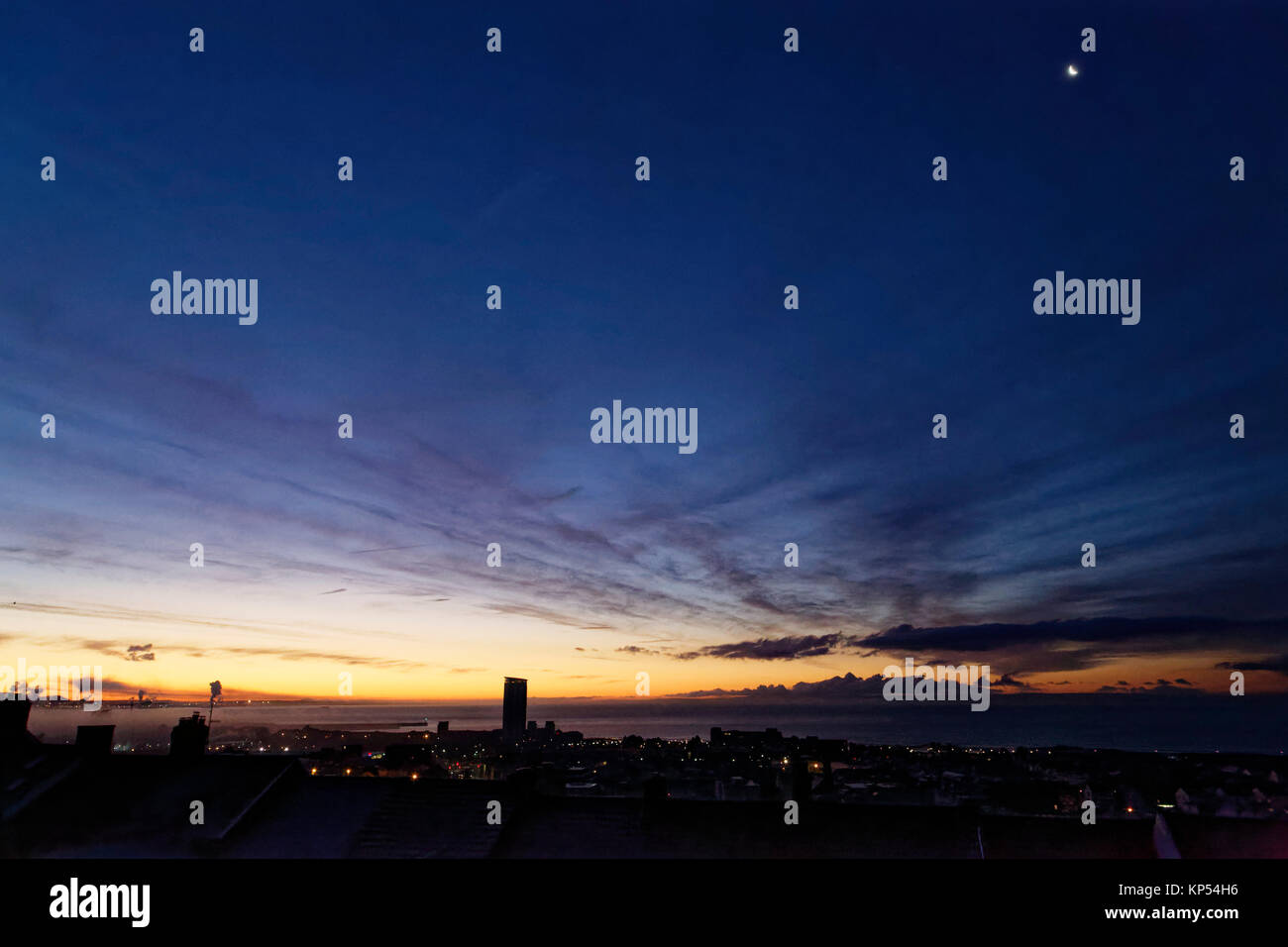 A crescent moon is still visible in the clear sky over roof tops during an early frosty morning in Swansea, Wales, - Stock Image