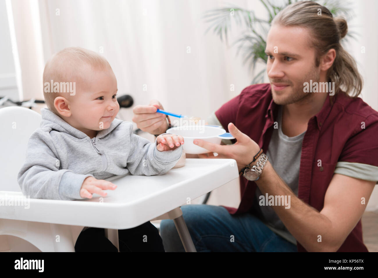 father feeding his cheerful son with baby food at home - Stock Image