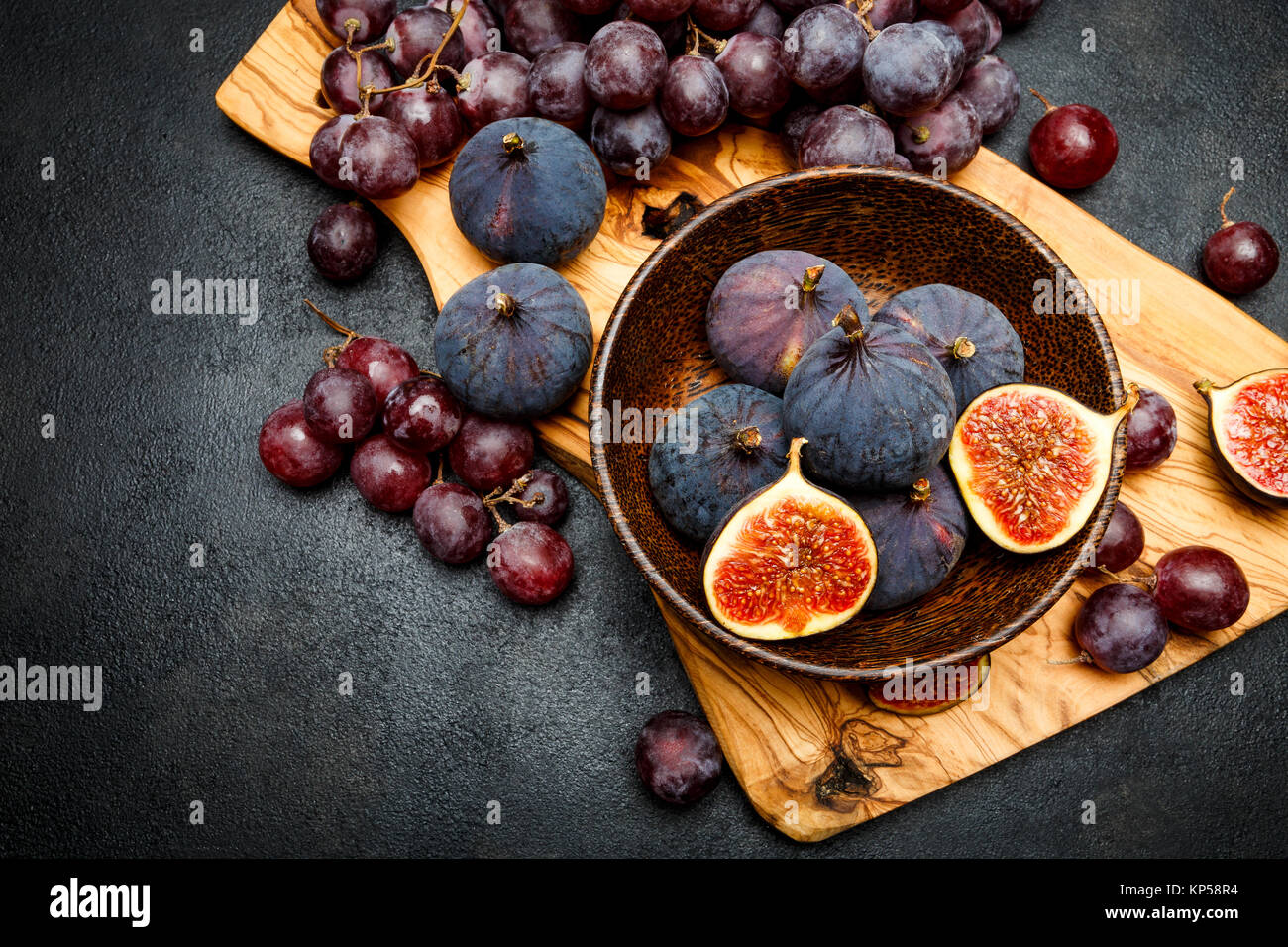 Ripe Grapes and Figs on dark concrete background - Stock Image