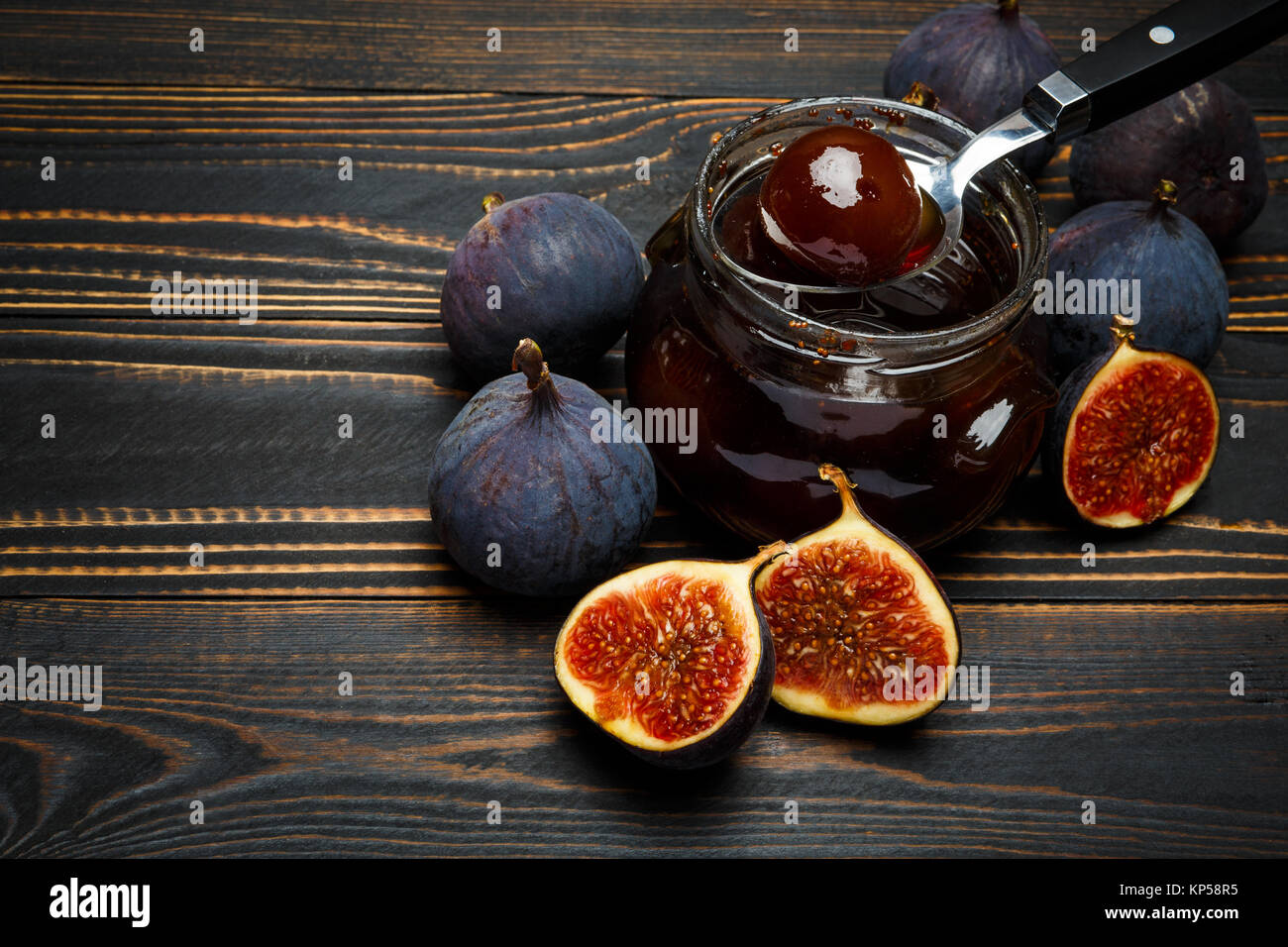 Glass jars full of fig jam and fig fruits on a dark wooden background - Stock Image