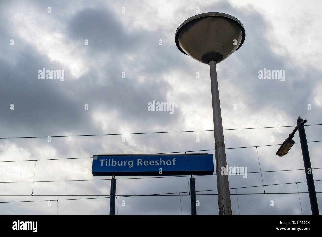 Tilburg, Netherlands. Namesign, streetlight and catenary at Tilburg-Reeshof railway station. Stock Photo