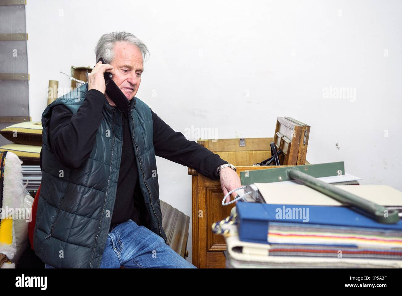 Tilburg, Netherlands. The 75 year old upholsterer Boy making his last phonecalls before partially retiring and moving - Stock Image