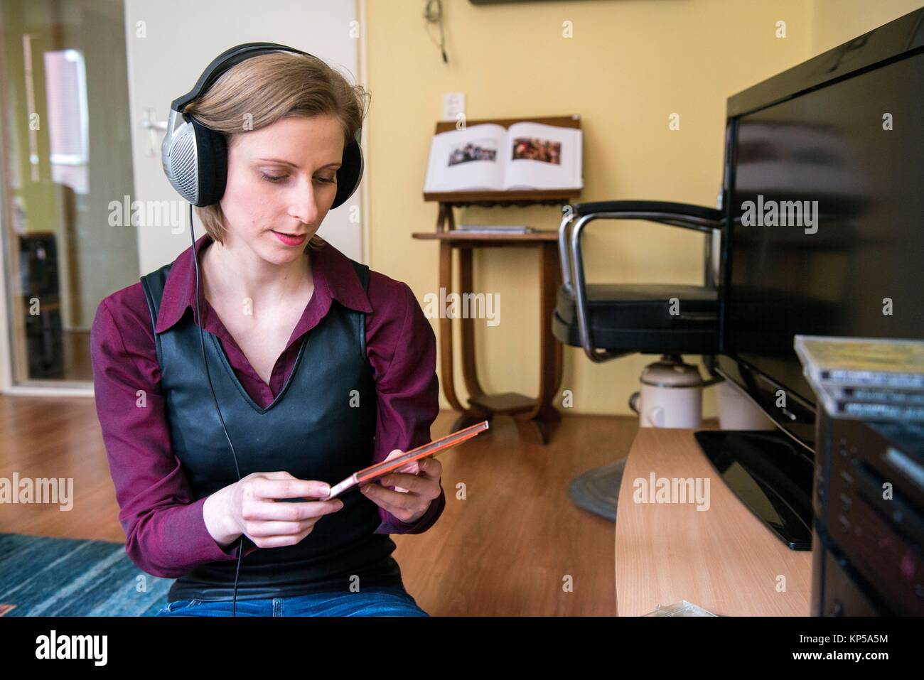 Tilburg, Netherlands. Young adult caucasian woman enjoying music from her stereo hifi set using a headset and a - Stock Image
