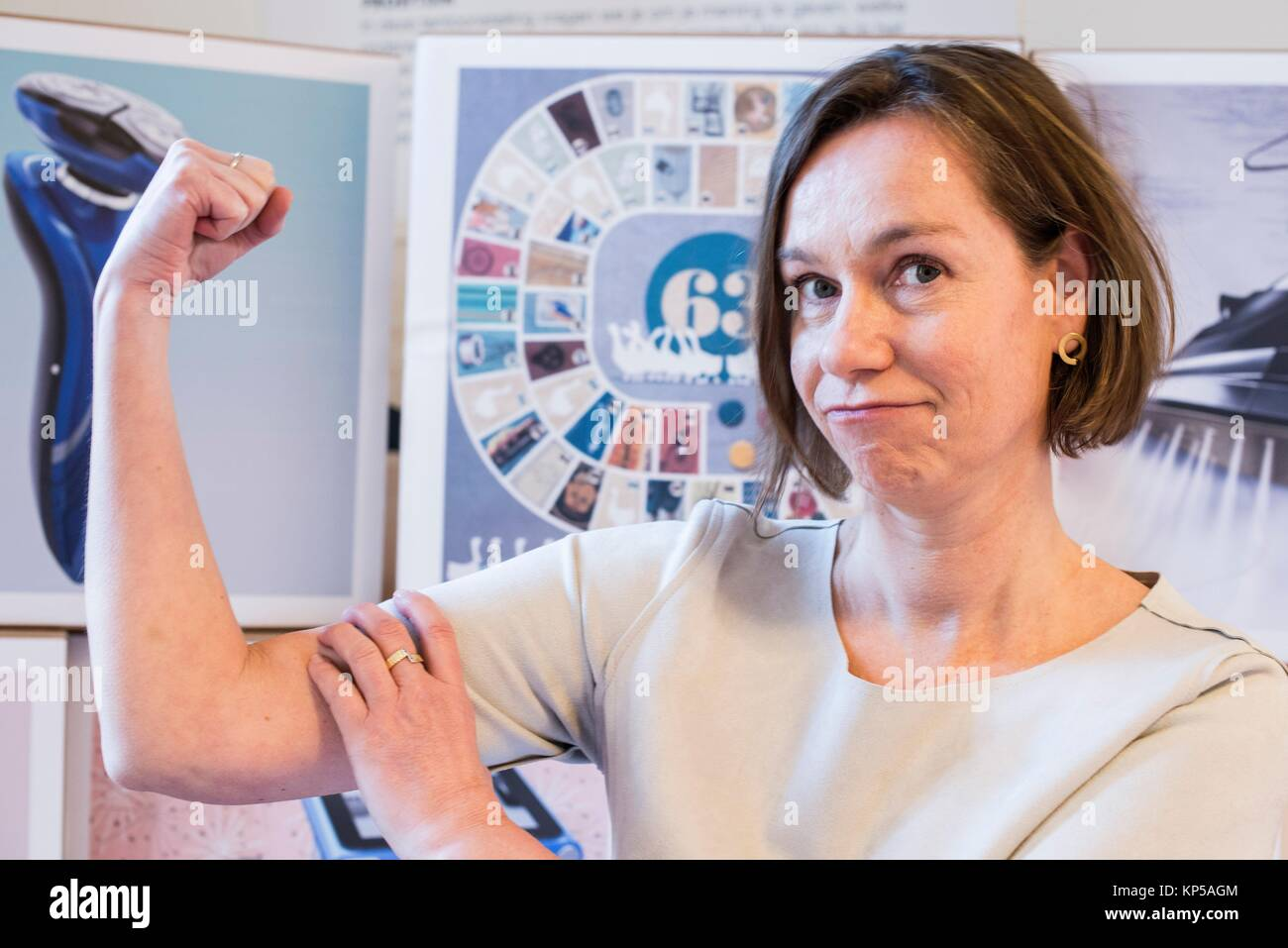 The Hague, Netherlands. Portrait of an adult caucasian woman showing her strength, while sitting in front of images - Stock Image