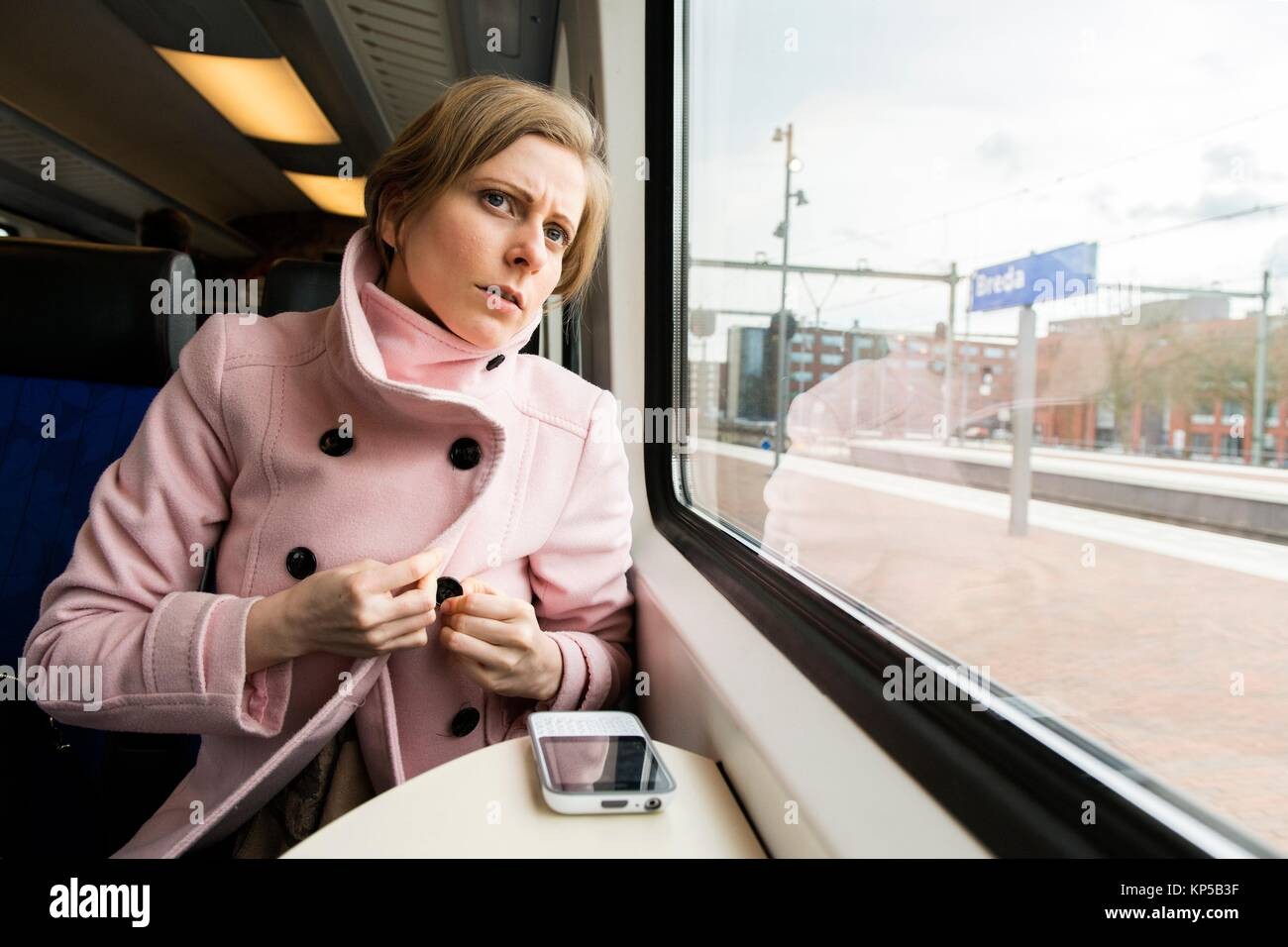 Tilburg, Netherlands. Young adult caucasian female commuting by intercity train to her assignmenet as a musical - Stock Image