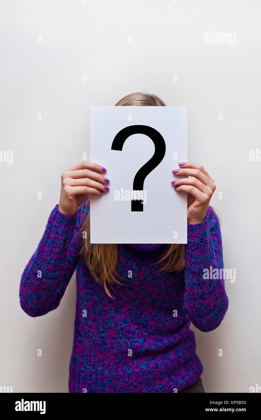 woman in purple sweater holding a white paper with a question mark - Stock Image
