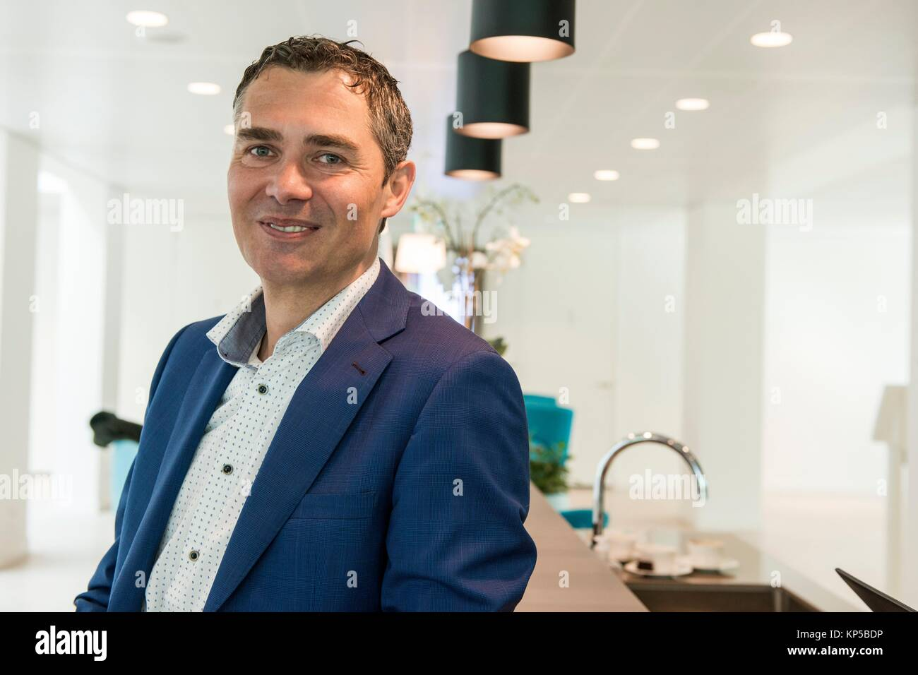 Geldrop, Netherlands. Editorial portrait of a male, caucasian banker at his bank-office reception desk. - Stock Image