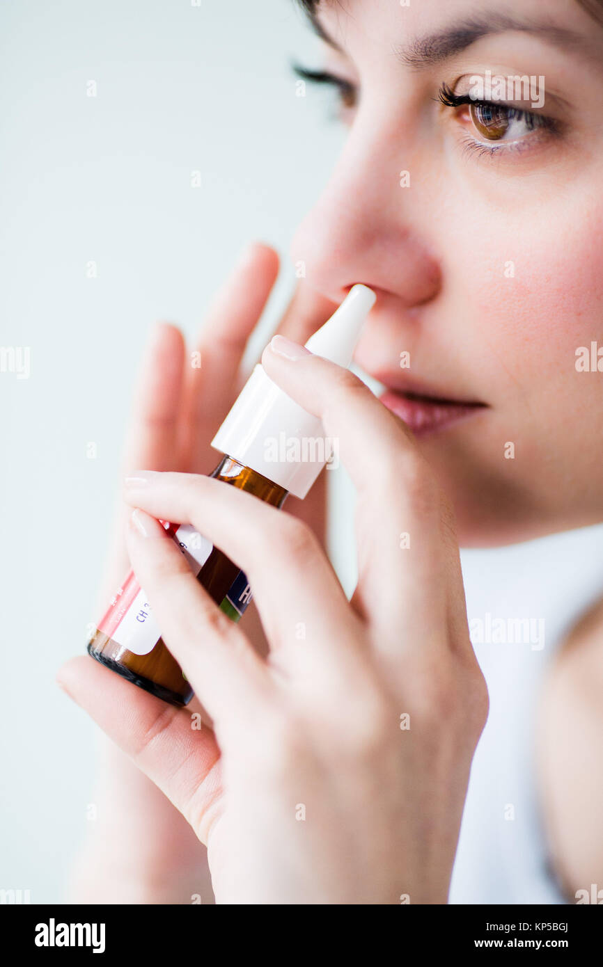 Woman using an antihistamine spray in the treatment of rhinitis allergy. - Stock Image