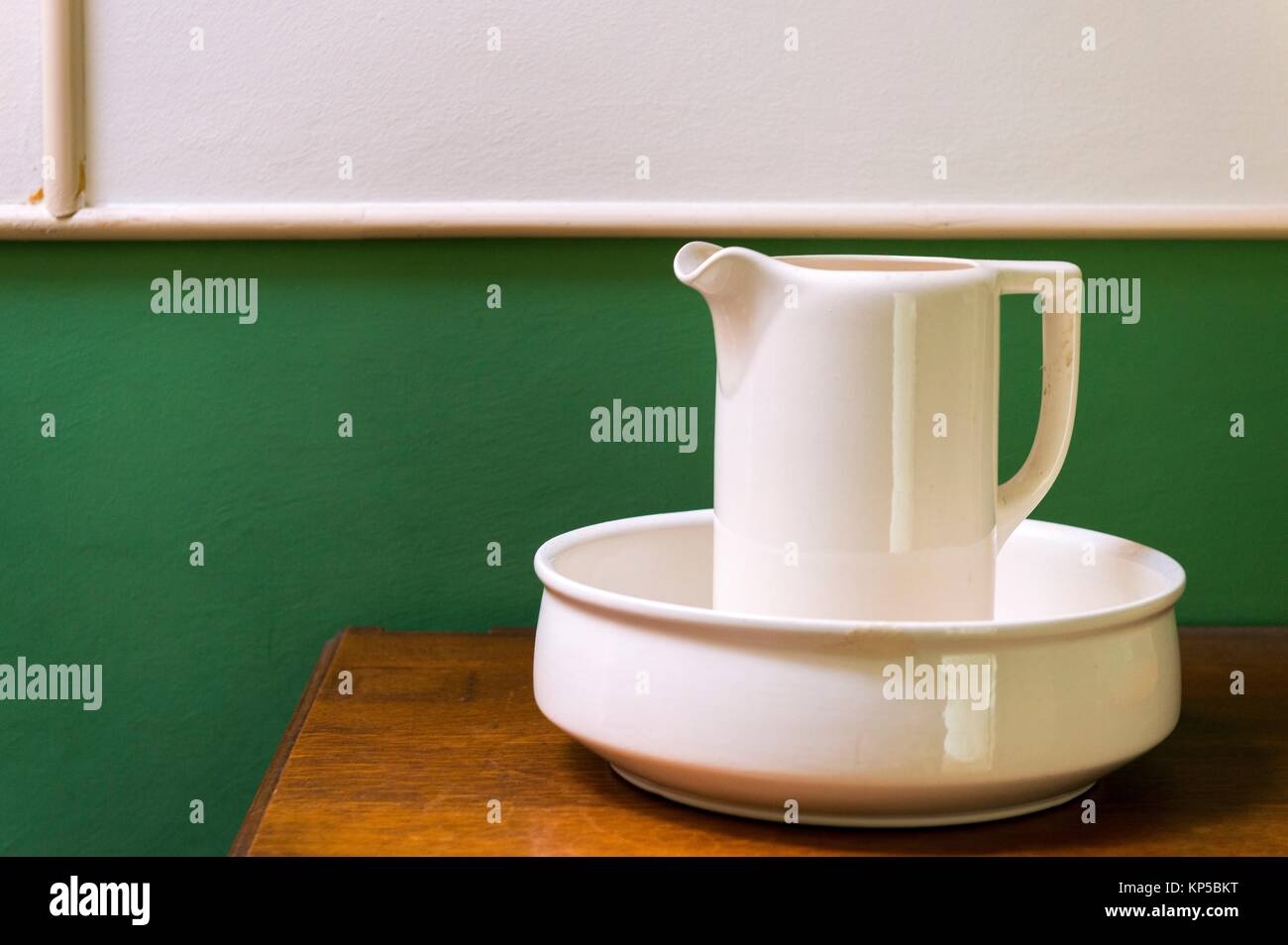 Tilburg, Netherlands. Ewer, watercan and bowl placed on a dressoir against a green and white interior wall. Stock Photo
