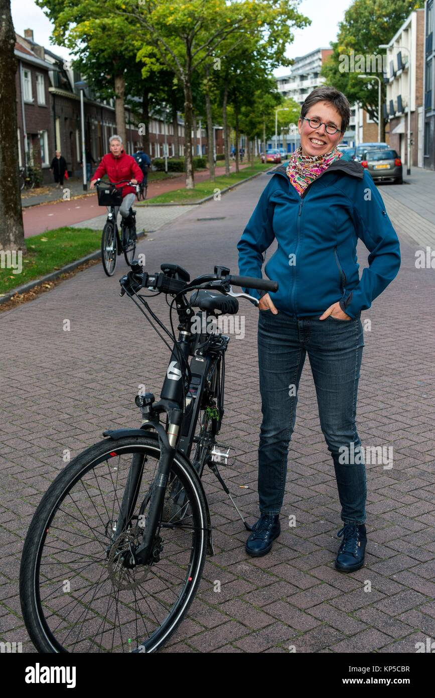 Tilburg, Netherlands. Mature adult caucasian woman and Multiple Sclerosis patient still riding her bike coping with - Stock Image
