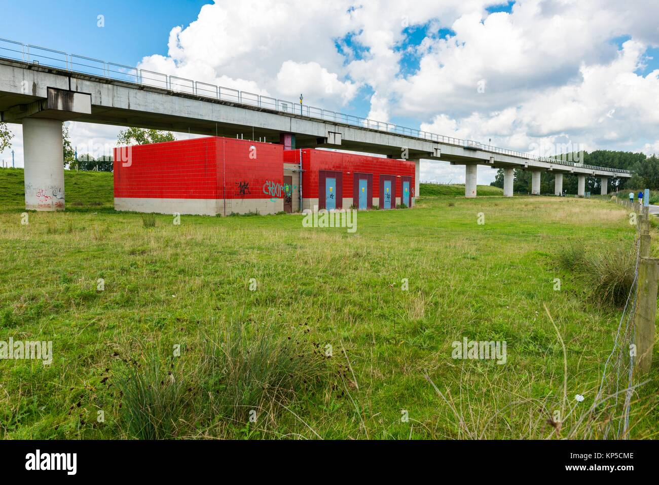 Poortugaal, Netherlands. Electrical transformation building for subway power beneith an elevated subway track and - Stock Image