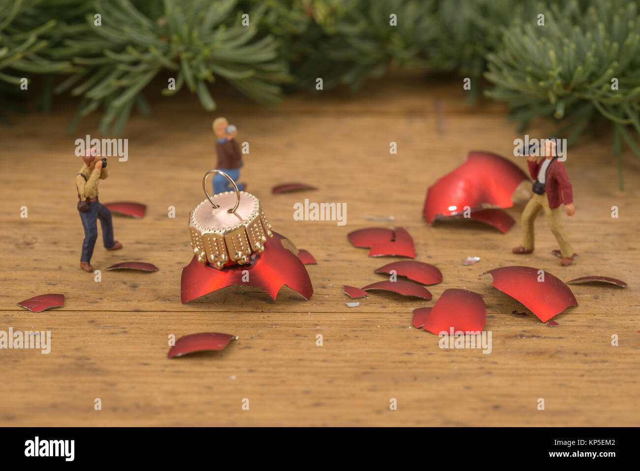 Miniature people photographers figures at broken red christmas balls - Stock Image