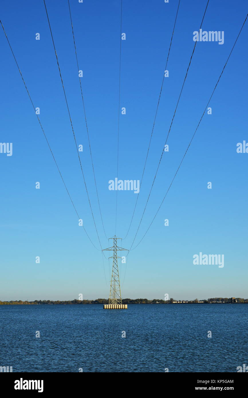 Power transmission Tower in a lake isolated against a bright blue sky - Stock Image