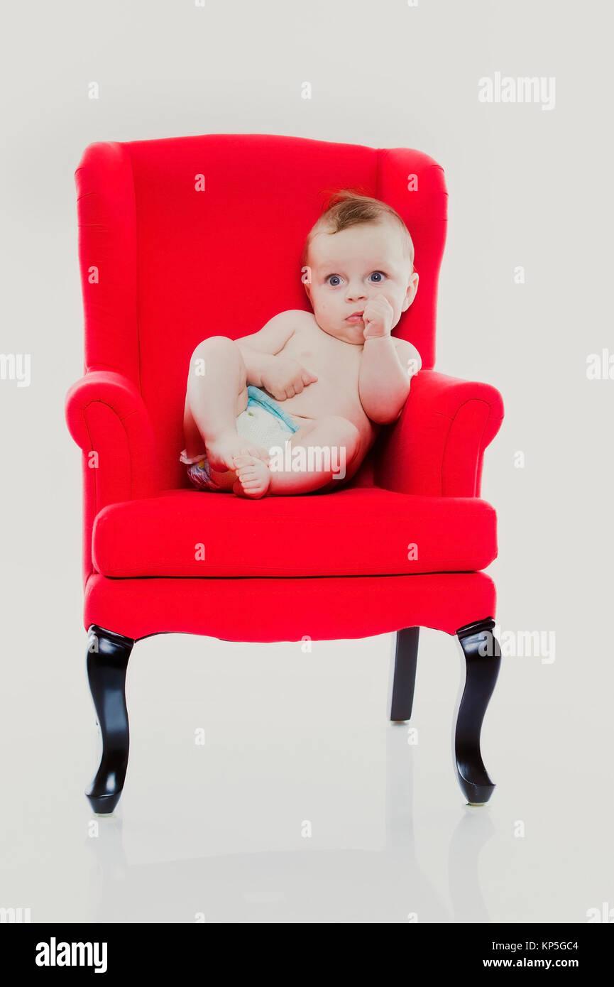 Baby, 4 Monate, sitzt auf einem roten Stuhl - baby sitting on a red chair - Stock Image