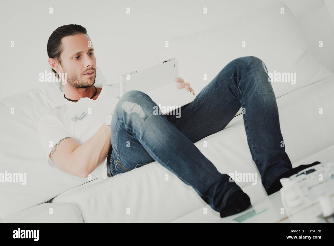 Mann mit IPad auf der Couch - man with Ipad sitting on a couch - Stock Image