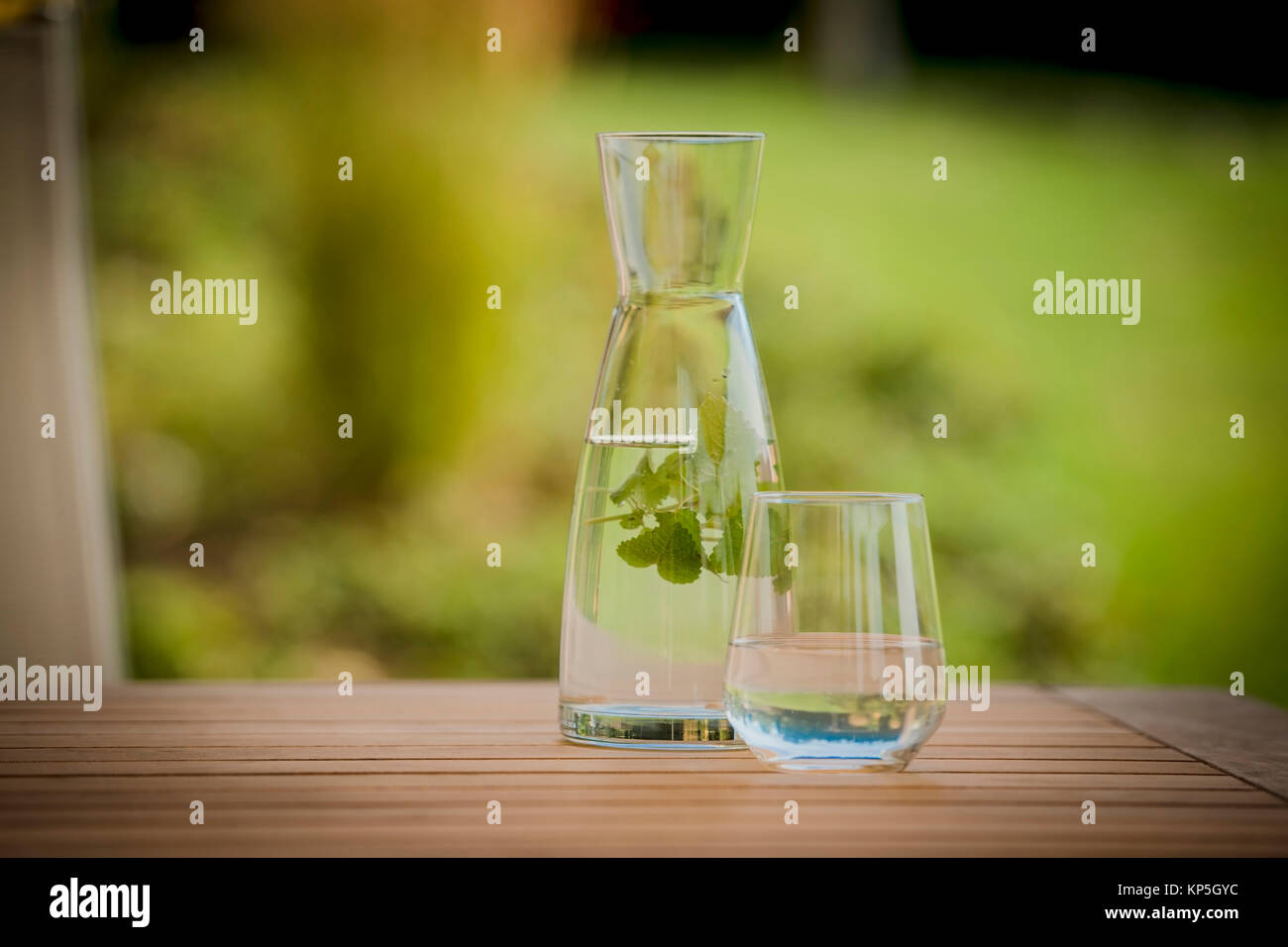 Wasserkrug- und glas mit Kraeutern - water jar with herbs Stock Photo