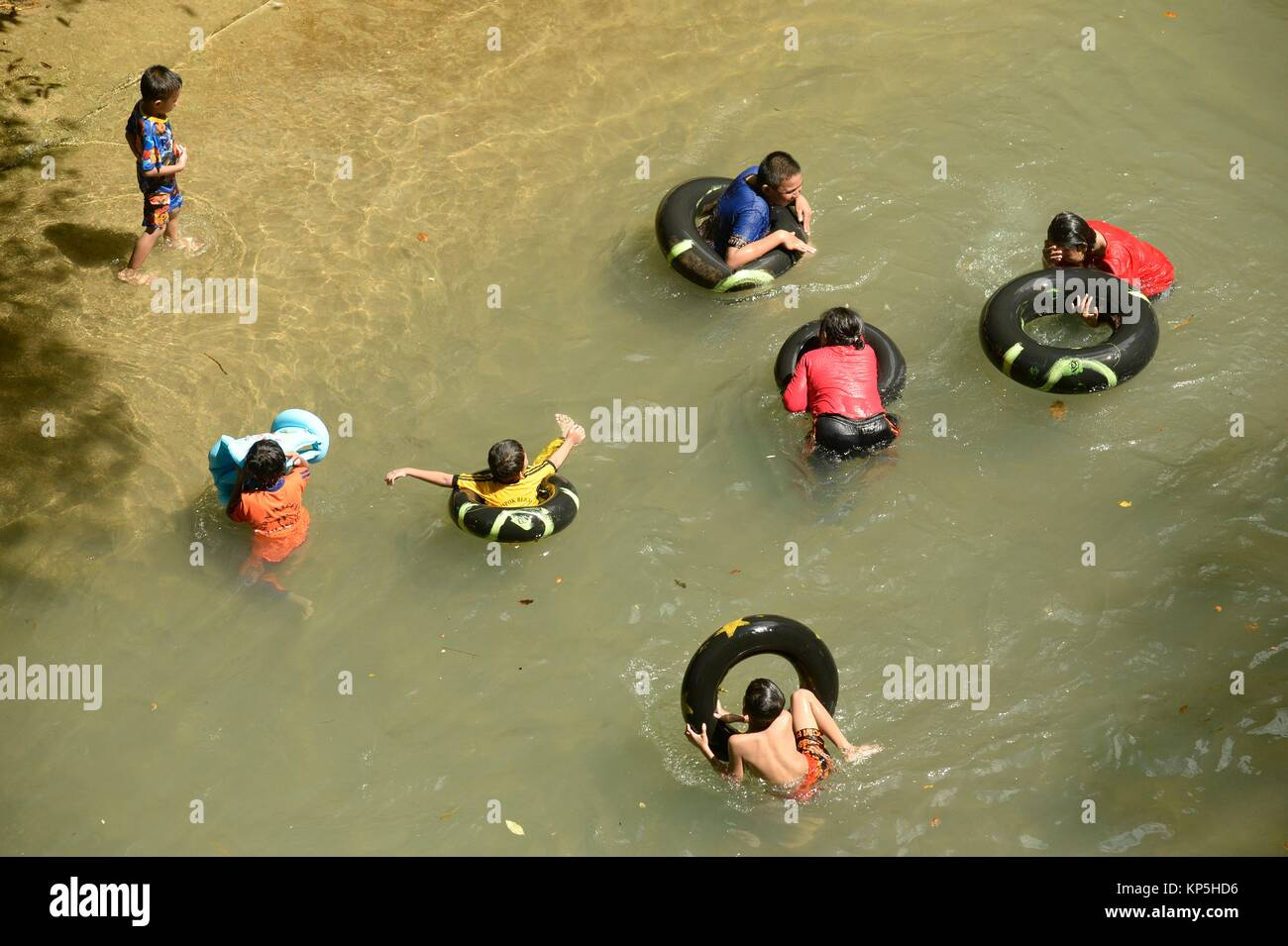 Children floating in the water using tyre swim float,Bantimurung water park,Sulawesi, Indonesia. - Stock Image