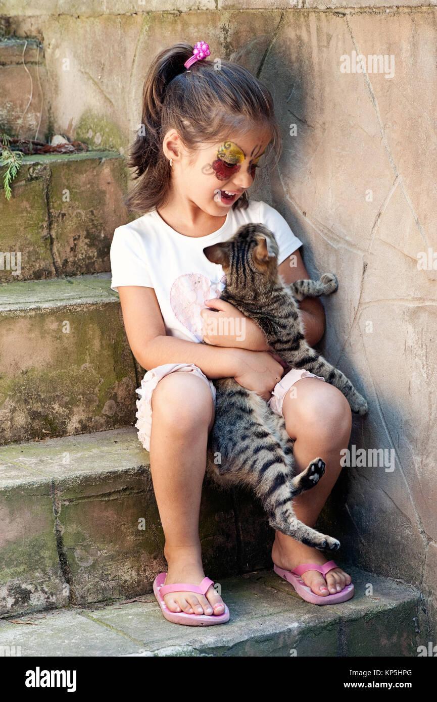 Little girl hugging tabby cat - Stock Image