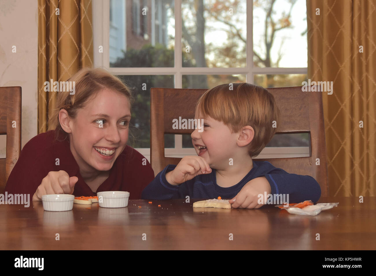 Mother and Son sitting in kitchen together decorating cookies - Stock Image