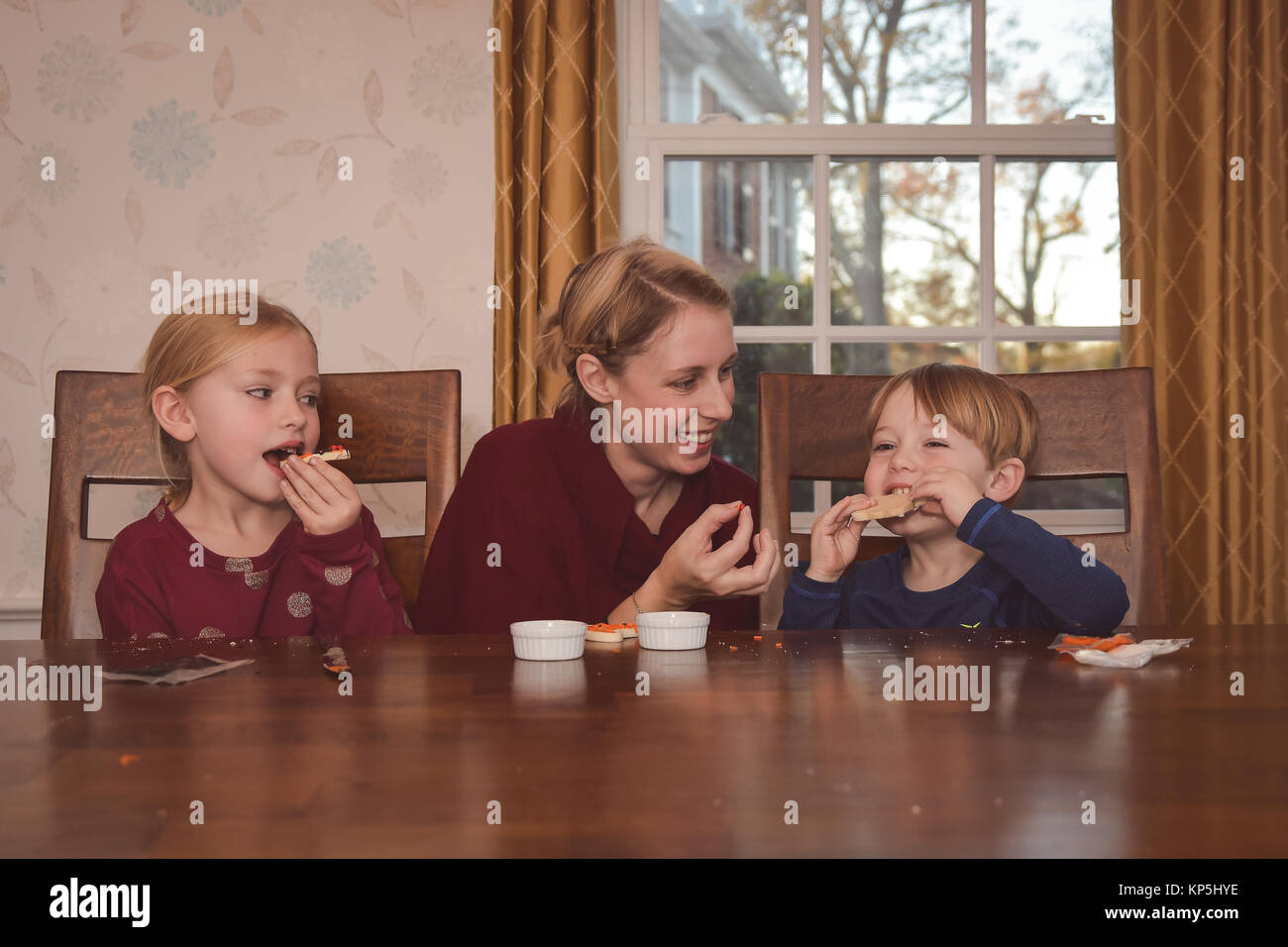 mother sitting with 2 children decorating cookies - Stock Image