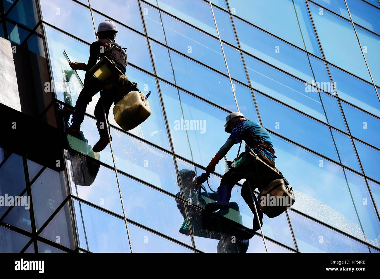 Male window washer cleaning the windows of a glass high ...