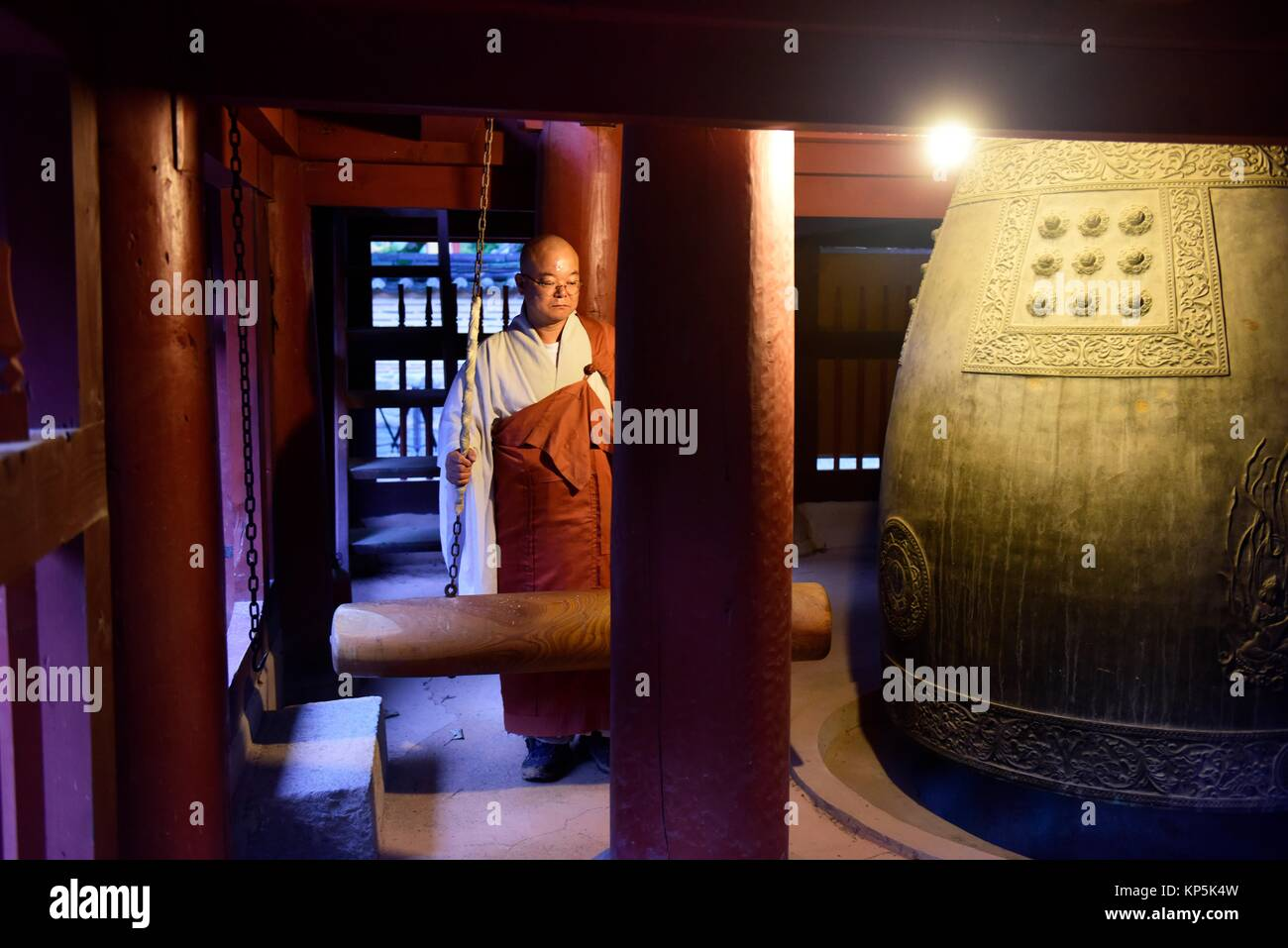 A monk calls the monks together by hitting a bell at Baekyangsa temple in Naejangsan National Park,South Korea. - Stock Image