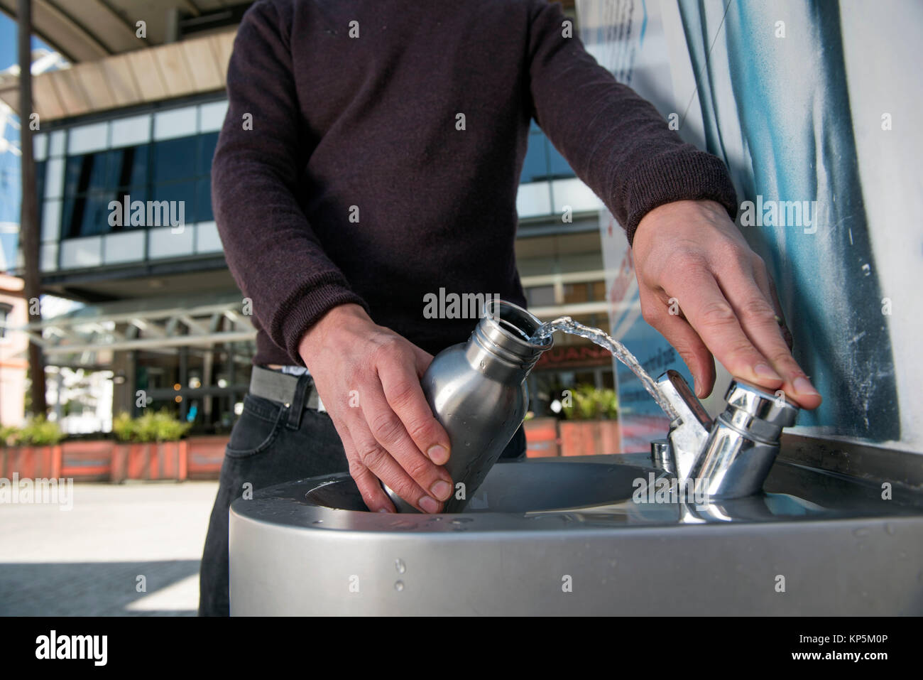 'City To Sea', a campaign to rid Bristol of plastic bottle waste - a student refills his water bottle in Millennium - Stock Image
