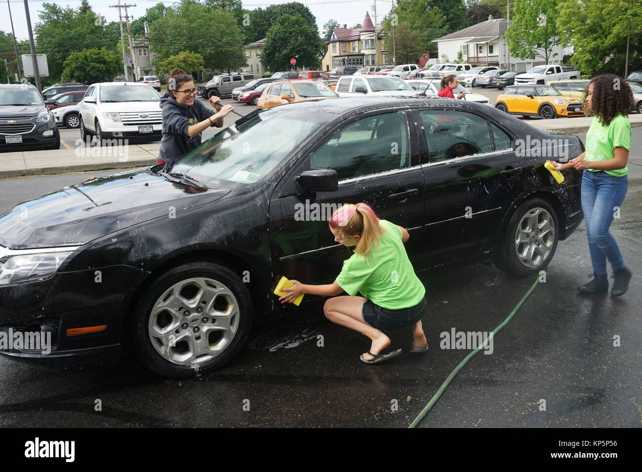 Middle School Girls Washing Car for Community Service Day, Wellsville, New York, USA. - Stock Image