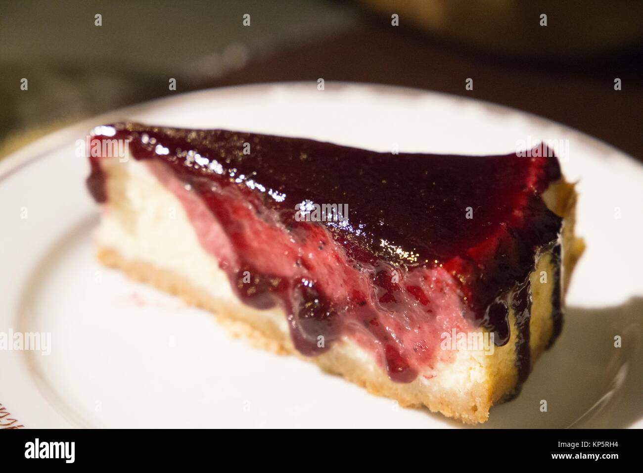 Piece of cheesecake topped with cherry compote - Stock Image