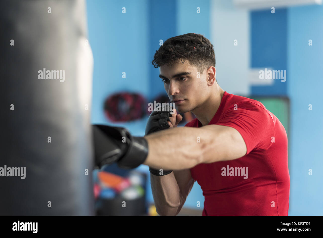 Boxer in gym training with punching bag - Stock Image