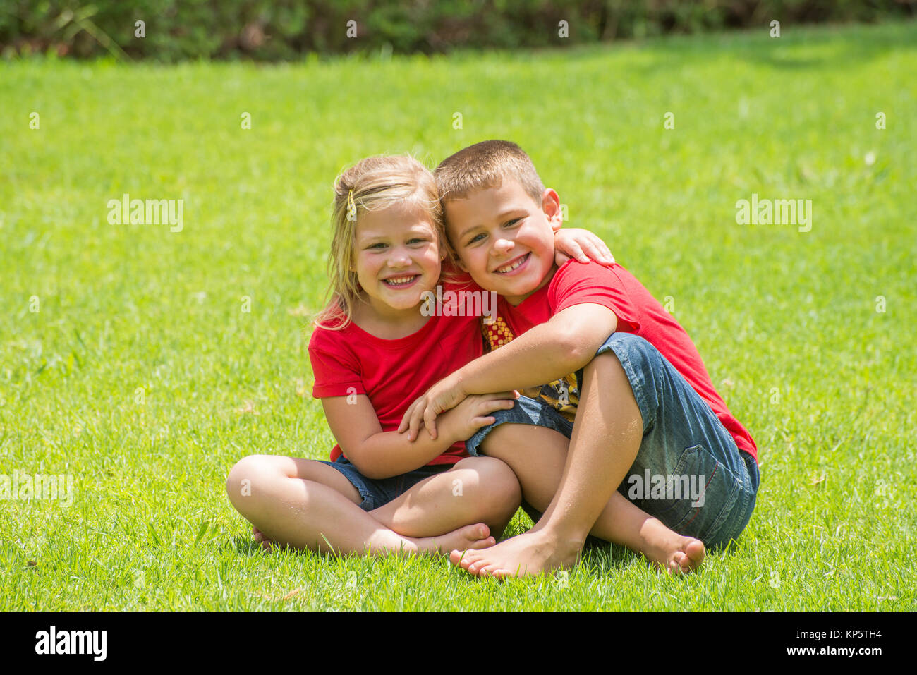 Brother ans Sister in Red on Lawn - Stock Image