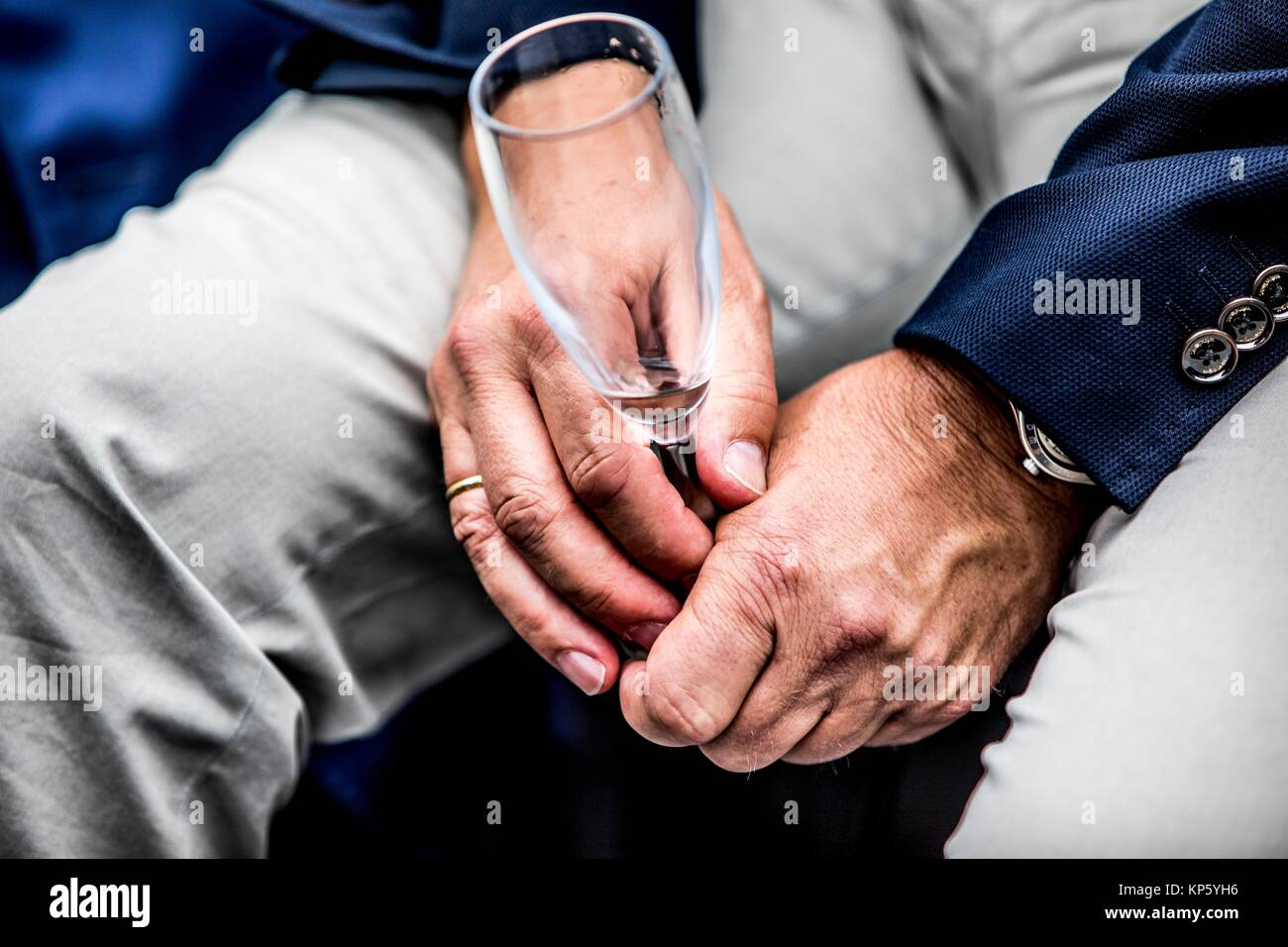 Close-up of male hands with empty champagne flute. - Stock Image