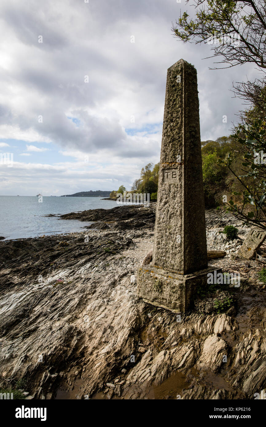Stone obelisk on the rocky foreshore of the Carrick Roads near Falmouth at Penarrow Point carved with initials TB - Stock Image