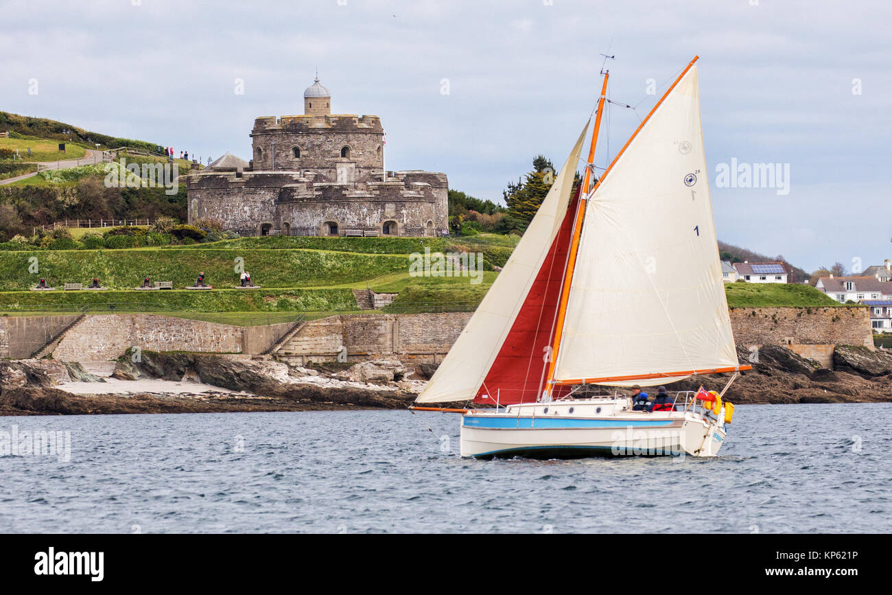 Small yacht with red and white sails passing St Mawes Castle on the Roseland peninsula in Cornwall UK - Stock Image