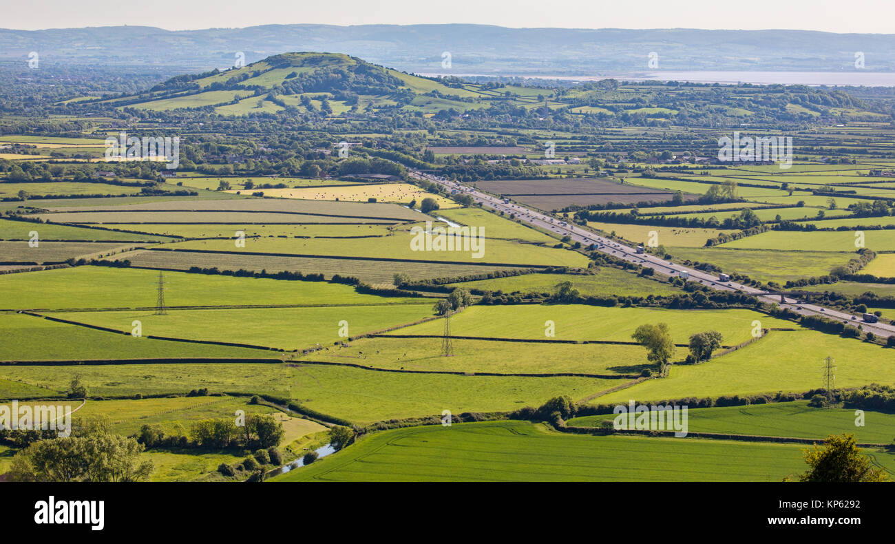 View over the Somerset levels towards Brent Knoll and Bridgewater Bay with the M5 motorway in the foreground - Somerset - Stock Image