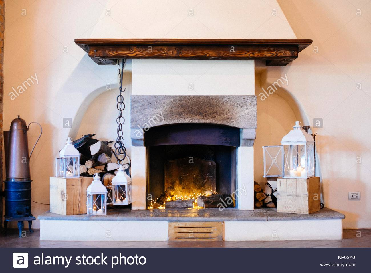 Fireplace decorated with lights and lamps - Stock Image