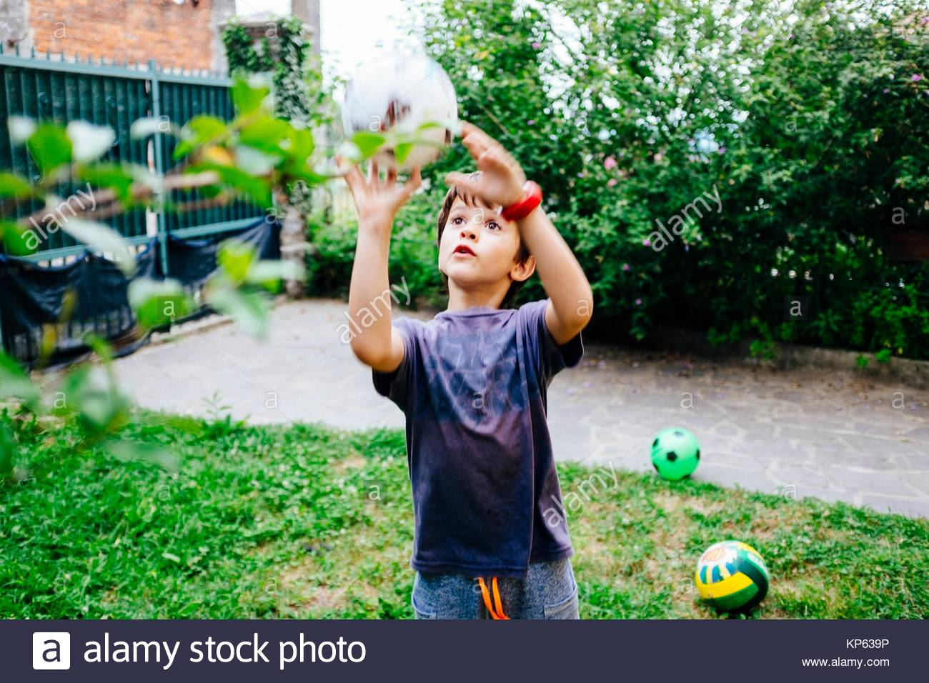 child plays ball in the garden of the house - Stock Image