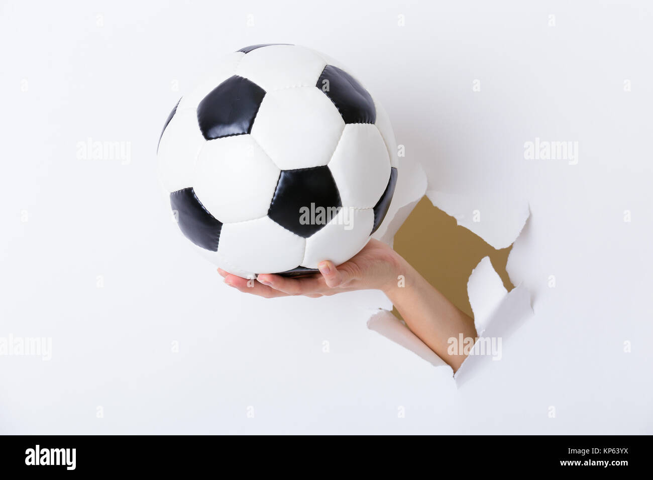 Hand holding soccer ball through the paper hole - Stock Image