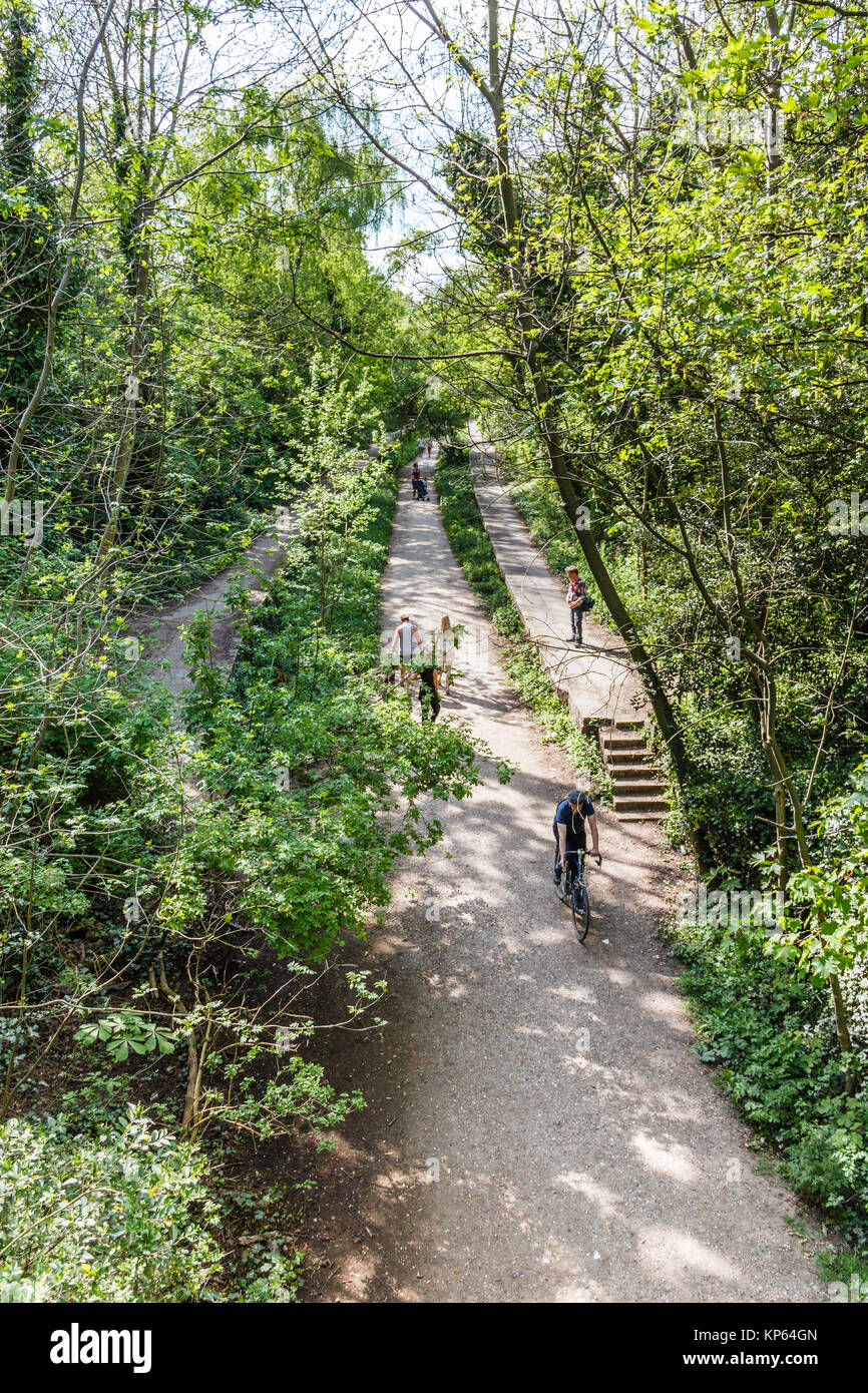 Walkers and cyclists on Parkland Walk, a disused railway line, now a conservation area, in North London, UK - Stock Image