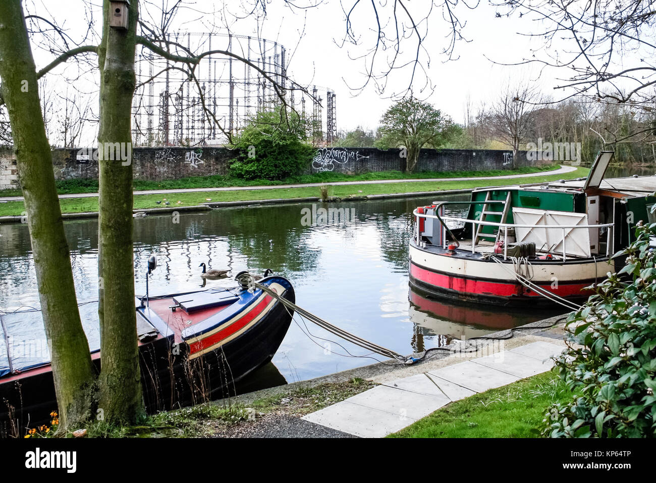 Narrowboats on Regent's Canal at Kensal Green, London, UK,  the disused gasometers in the background Stock Photo